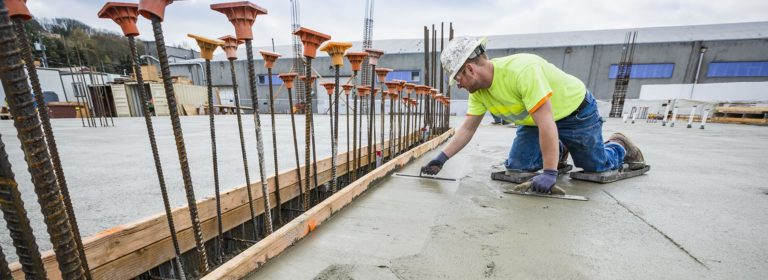 A concrete contractor creating a finished surface on fresh concrete.